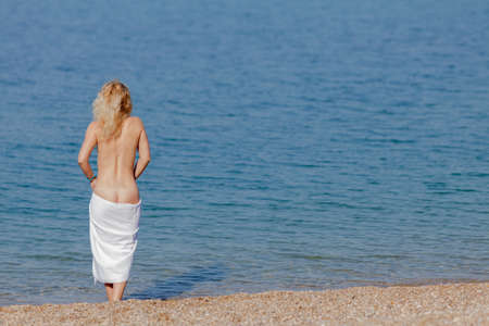 Female person resting at the sea. Blonde woman with white beach towel on hips entering in water