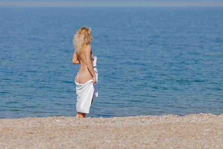Persona femenina descansando en el mar. Mujer rubia envuelta en una toalla de playa blanca se encuentra en la orilla del mar y mira a la distancia Foto de archivo