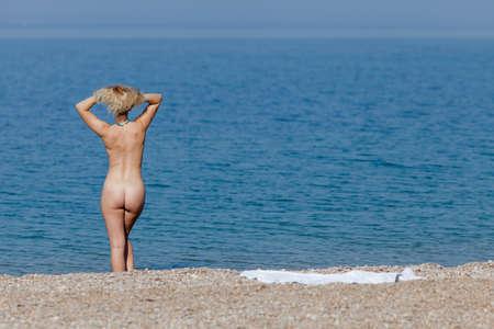 Weibliche Person, die am Meer stillsteht. Nackte junge Frau, die mit den Armen hinter dem Kopf ins Meer eindringt Standard-Bild