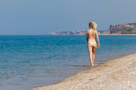 Nacktes Mädchen, das am Meer stillsteht. Blonde Frau, die am Wasserrand entlang geht