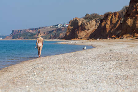 Seascape with naked girl. Blonde woman walking along empty pebble beach Standard-Bild