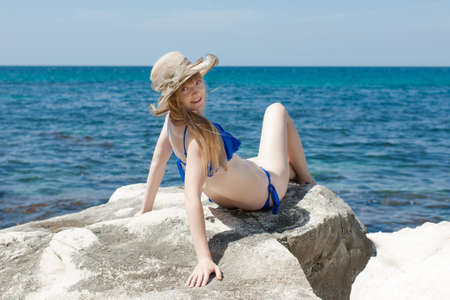 Portrait of white-skin girl in beach hat on wild seashore. Attractive female person in blue swimsuit and broad-brim hat sunbathes on rocky beach