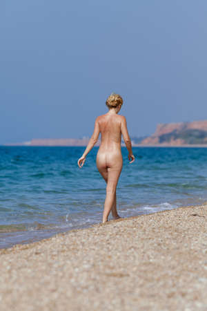 Naked slim woman resting on the beach. Blonde with collected hair walking along waters edge Stok Fotoğraf