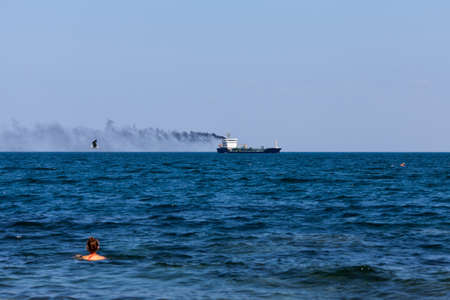 Seascape with a smoking ship. Black sea, swimming girl and seabird in windy day Imagens