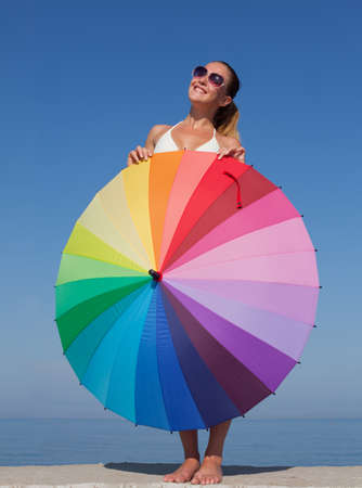 Portrait of girl with rainbow parasol. Attractive young woman hides under multi colored umbrella, she looks up smiling