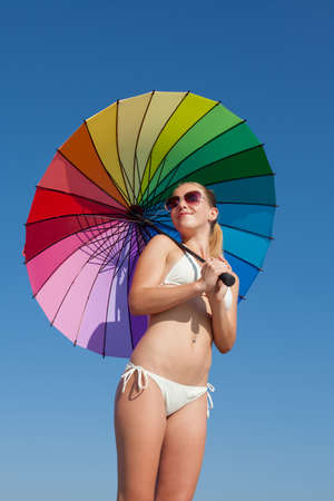 Portrait of girl under rainbow parasol. Attractive young woman holds multi colored umbrella behind him 版權商用圖片