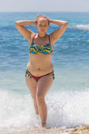 Overweight female person resting at the sea. Young chubby woman in bikini comes out from seawater with hands behind head