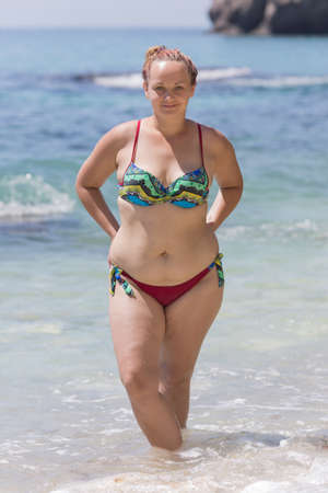 Overweight female person resting at the sea. Young chubby woman in bikini posing with arms akimbo. She stands ankle-deep in water and looks at camera smiling a little