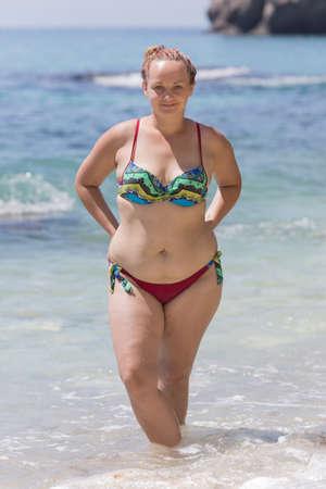 Persona de sexo femenino con sobrepeso descansando en el mar. Mujer gordita joven en bikini posando con los brazos en jarras. Ella se para en el agua hasta los tobillos y mira a la cámara sonriendo un poco
