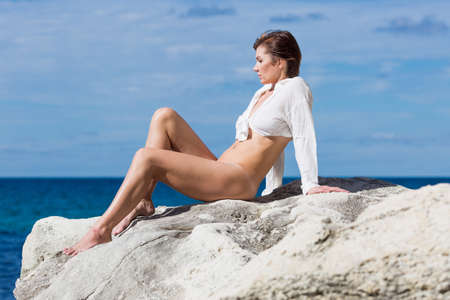 Female person resting on wild rocky seashore. Half-naked  woman in full unbuttoned, knotted shirt sunbathing on coastal rock. She sits leaning on hands and bending knees