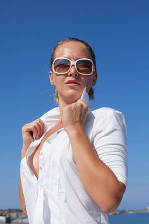 Waist-up portrait of girl in white unbuttoned blouse. Young woman in tinted sunglasses posing outdoors with serious face