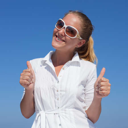 Waist-up portrait of girl in white blouse and tinted sunglasses. Young woman in sunglasses showing thumbs up and looking at camera smiling Imagens