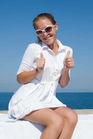 Portrait of girl in white short dress and tinted sunglasses. Young woman in sunglasses sitting on concrete wall, showing thumbs up and looking at camera smiling Imagens