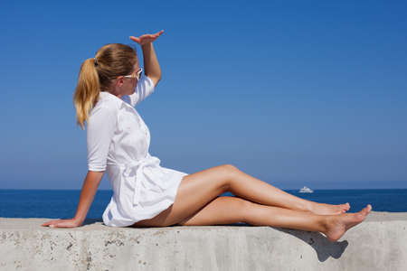 Barefoot girl in white short dress sits leaning on hand and looking away with hand visor. Young woman with ponytail hairstyle reclines on concrete wall and looks into distance Stock Photo