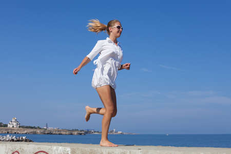 Barefoot girl in white short dress running along breakwater. Young woman with ponytail hairstyle jogs along concrete pier against sea Stock Photo