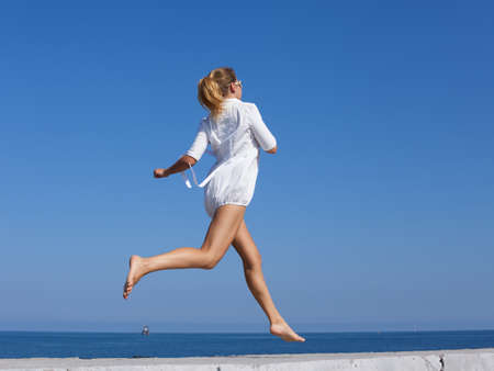 Barefoot girl in white short dress running along breakwater. Young woman with ponytail hairstyle jogs along concrete pier against sky, rear view