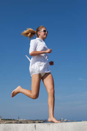 Barefoot girl in white short dress running along breakwater. Young woman with ponytail hairstyle jogs along concrete pier against sky