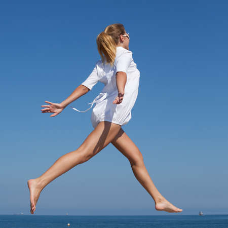 Barefoot girl in white short dress running along breakwater. Young woman jogs with hands outstretched along concrete pier against sky Stock Photo