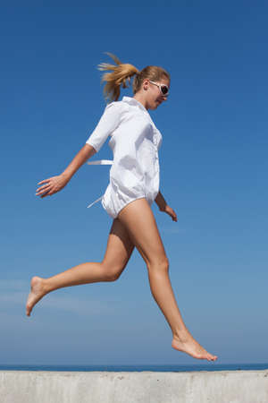 Barefoot girl in white short dress jogs on concrete construction. Young woman with ponytail hairstyle runs against sea Stock Photo