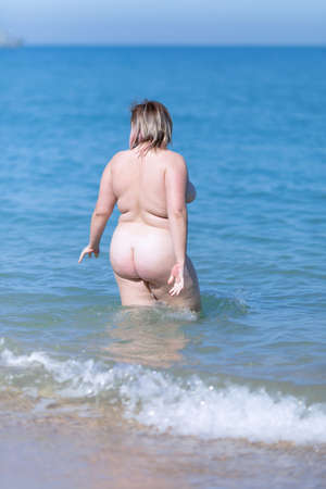 Overweight young woman at the sea. Naked overweight woman enters the sea water, rear view