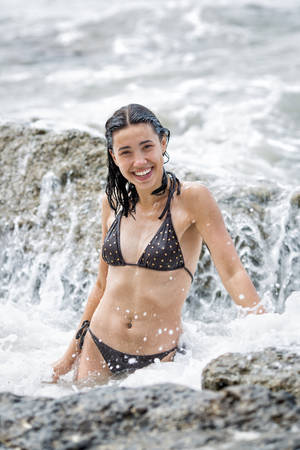 Attractive slim girl bathing in sea in cloudy day. Young female person stands waist-deep in sea foam laughing and looking at camera Banque d'images - 126857219