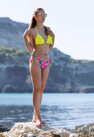 Portrait of girl in swimsuit and sunglasses on rocky seashore. Attractive young woman in bikini posing on coastal rock against picturesque shore Banque d'images - 126821590