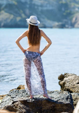 Rear view of girl in hat, swimsuit and sarong. Young woman posing with arms akimbo on coastal stone Banque d'images - 126821595
