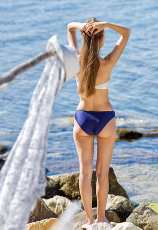 Rear view of long-haired girl in swimsuit. Young woman posing with hands behind head on seashore Banque d'images - 126821596