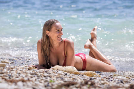 Girl in red bikini on pebble seashore. Young female person in swimsuit lies in waters edge, smiles and looks on away