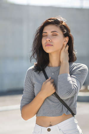 Late-teens girl walking in town in morning time. Waist-up portrait of eighteen-year-old girl with eyes closed