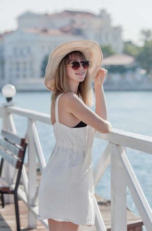 Three quarter length portrait of long-haired blonde woman on seafront. Young woman posing in hat and sunglasses on pier Banque d'images - 126821609