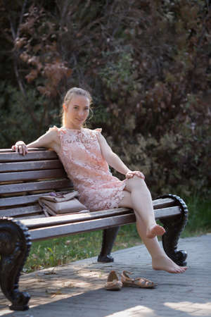 Thin girl resting in park in early time. Slim young woman in soft pink dress sits barefoot on bench in park Banque d'images - 126821614