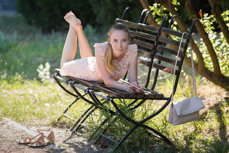 Thin girl resting in park in early time. Slim young woman in soft pink dress lies barefoot on bench in park Banque d'images - 126821637