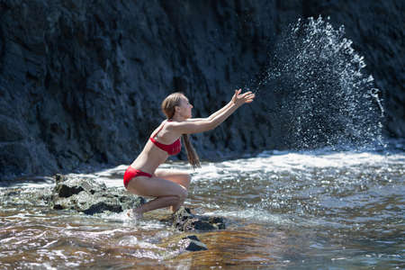 Young woman plays with seawater against dark cliff. Long-haired female person in red bikini sits squat and splashing