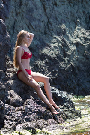 Young woman posing on coastal rock. Long-haired female person in red bikini sits on rock near waters edge Banque d'images - 127390871
