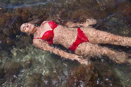Girl in red bikini lies on seawater. Young woman swims on back with eyes closed Banque d'images - 127390877