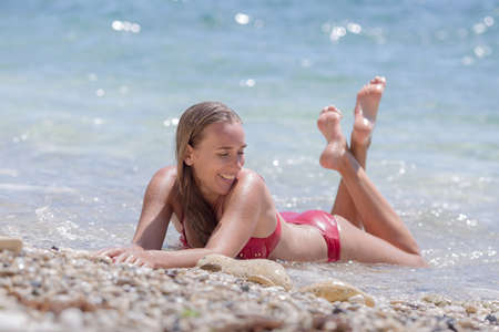 Girl at sea in time of surf. Young woman lies on front in seawater smiles and looks away