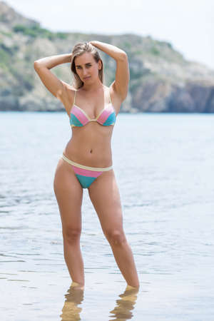 Young woman in swimsuit stands  ankle-deep in seawater with hands behind head. Slim female person in bikini poses at shallow with arms raised Banque d'images - 127175615