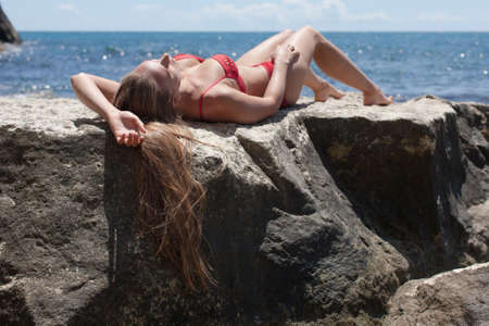 Beautiful woman sunbathing on coastal boulder. Attractive female person in red bikini lying on back on rock with knees bent and hand behind head
