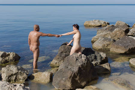 Middle age couple at the sea in summer day. Naked husband and wife resting on wild rocky seashore 스톡 콘텐츠