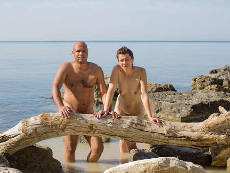 Portrait of middle age couple at the sea in summer day. Naked husband and wife posing on against sea