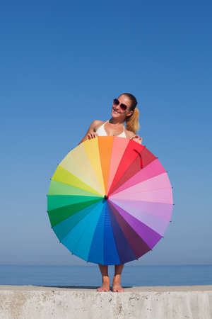 Portrait of girl with rainbow parasol. Attractive young woman hides under multi colored umbrella, she looks at camera smiling