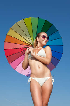 Portrait of girl under rainbow parasol. Attractive young woman holds multi colored umbrella behind him Фото со стока