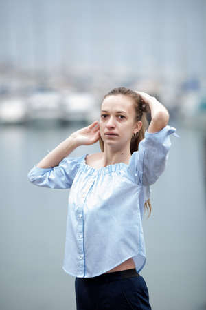 Portrait without make-up of female person in overcast day. Young woman posing with arms raised against bay Фото со стока