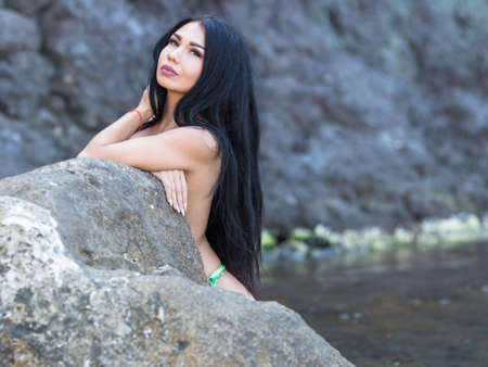 Attractive long haired brunette person resting at secluded place of wild rocky seashore. Half naked young woman in green swimming trunks hides behind coastal boulder Reklamní fotografie