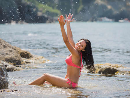 Girl resting on rocky seashore. Girl in pink bikini sits in shallow seawater and splashes. She smiles looking at camera