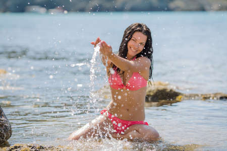 Girl resting on rocky seashore. Girl in pink bikini kneels in shallow seawater and splashes. She smiles looking at camera