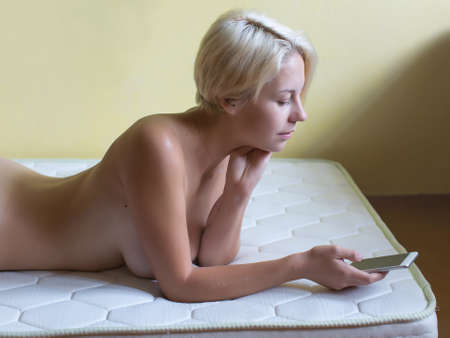 Young woman resting. Naked blonde woman lies on front on orthopedic mattress in room and reads messages on her smartphone