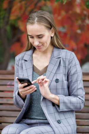 Portrait of attractive woman in the park. Businesswoman in gray suit  sits on bench in park and communicates on a smartphone