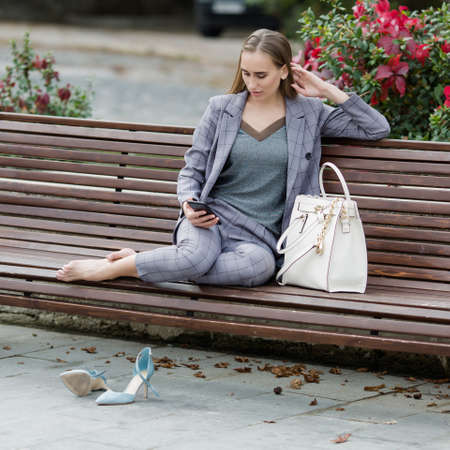 Barefoot woman sits on bench in park and communicates on a smartphone. Businesswoman in gray suit sitting with his feet on bench in park